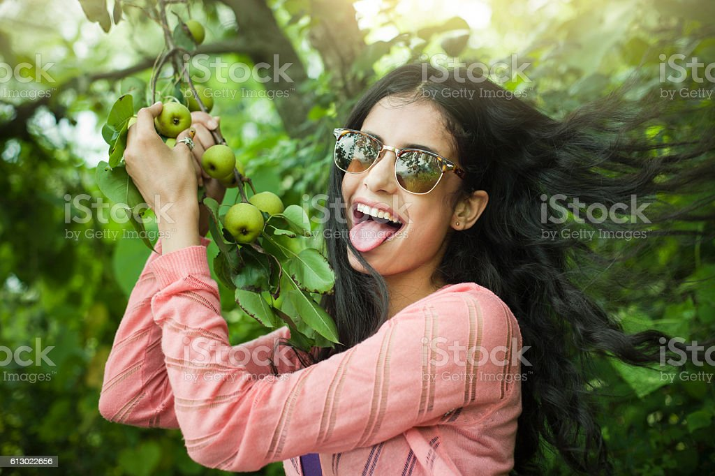 Beautiful girl showing tongue holding tree branch full of pear. stock photo