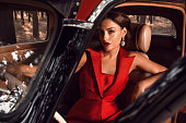 Beautiful girl sitting behind the wheel of vintage cars
