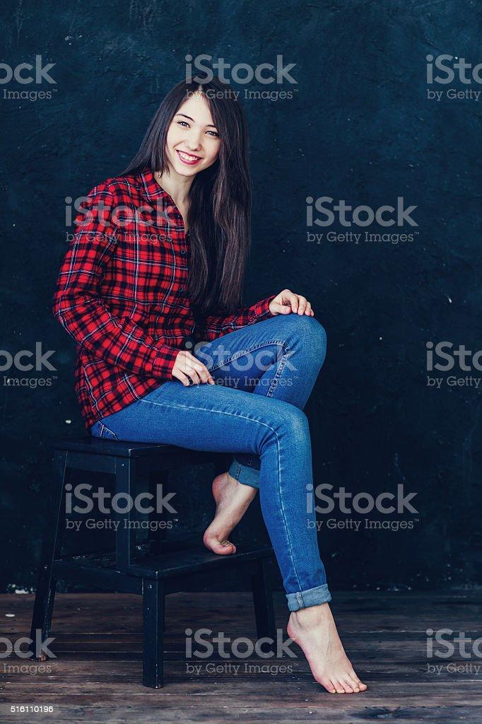 beautiful girl sitting on a chair in photo studio stock photo