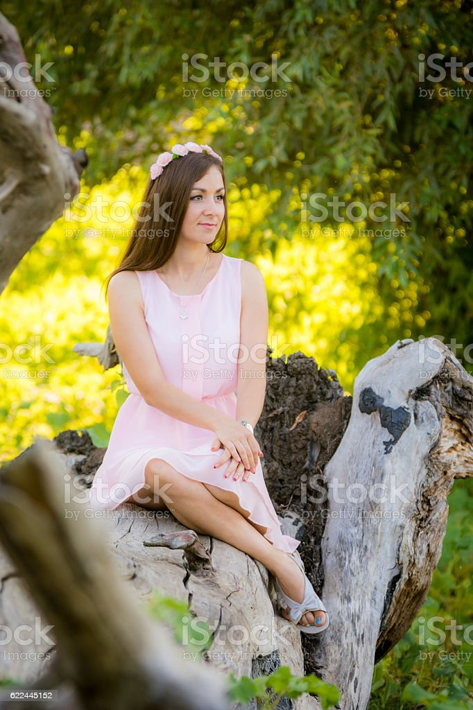 Beautiful girl sitting on a fallen tree in the forest stock photo