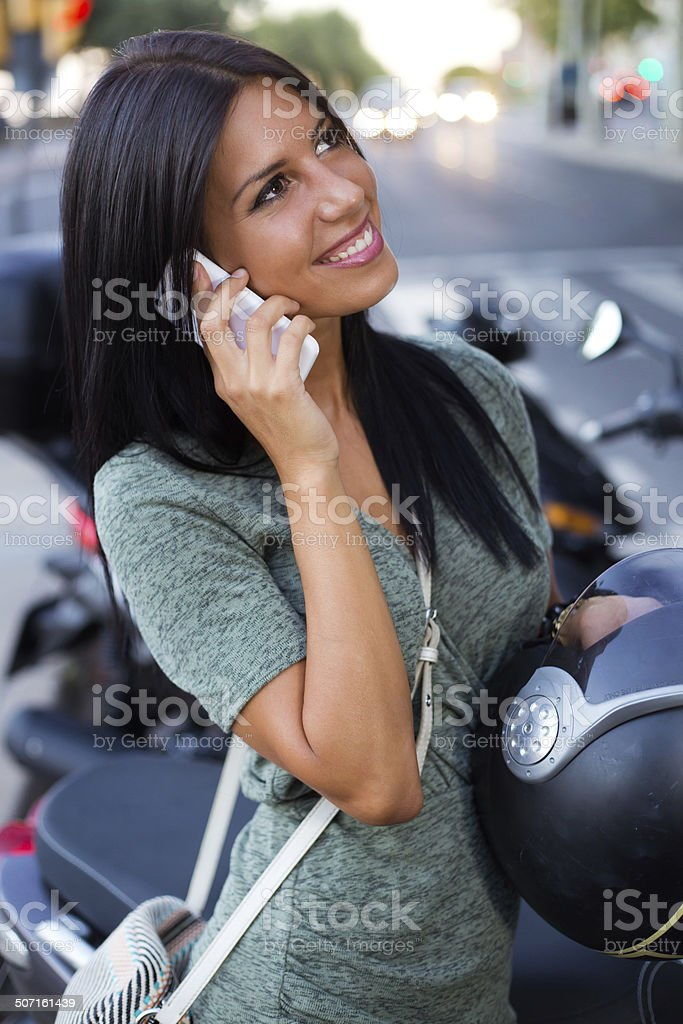 Beautiful girl sitting on a scooter and talking with phone. royalty-free stock photo