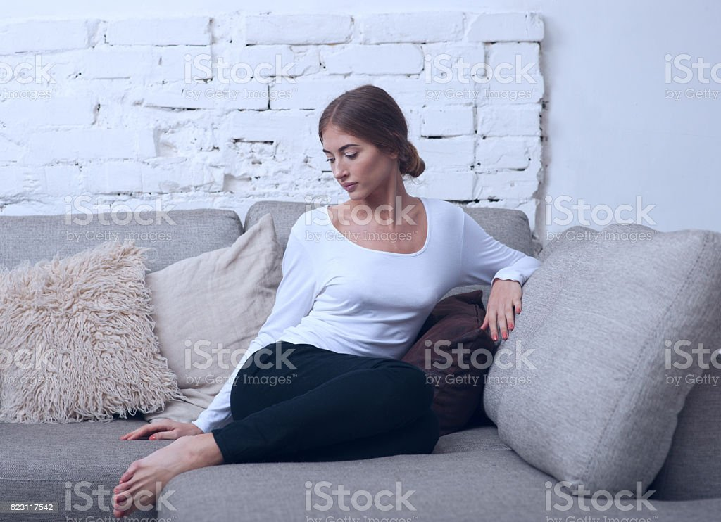 Beautiful girl sitting on a sofa in blue tones stock photo
