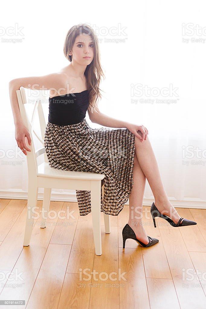 Beautiful girl sitting on chair stock photo