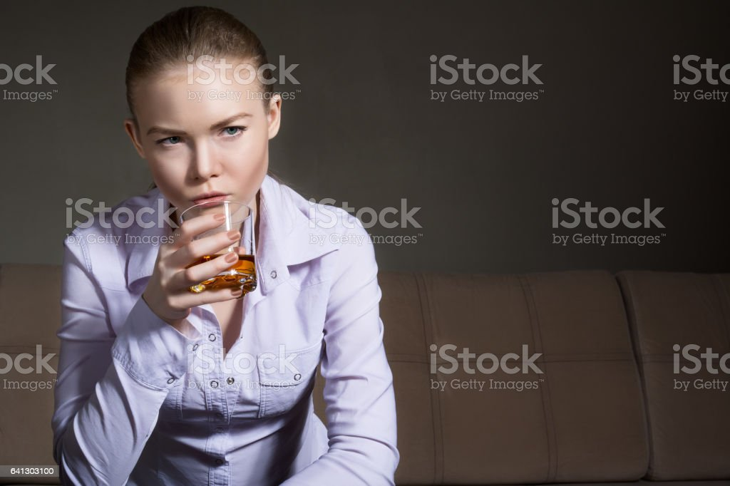 Beautiful girl sitting on the couch with a glass of whiskey. Blonde in a white shirt. Woman with alcohol in their hands. stock photo