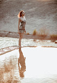 Beautiful girl sitting on the edge of a lake at
