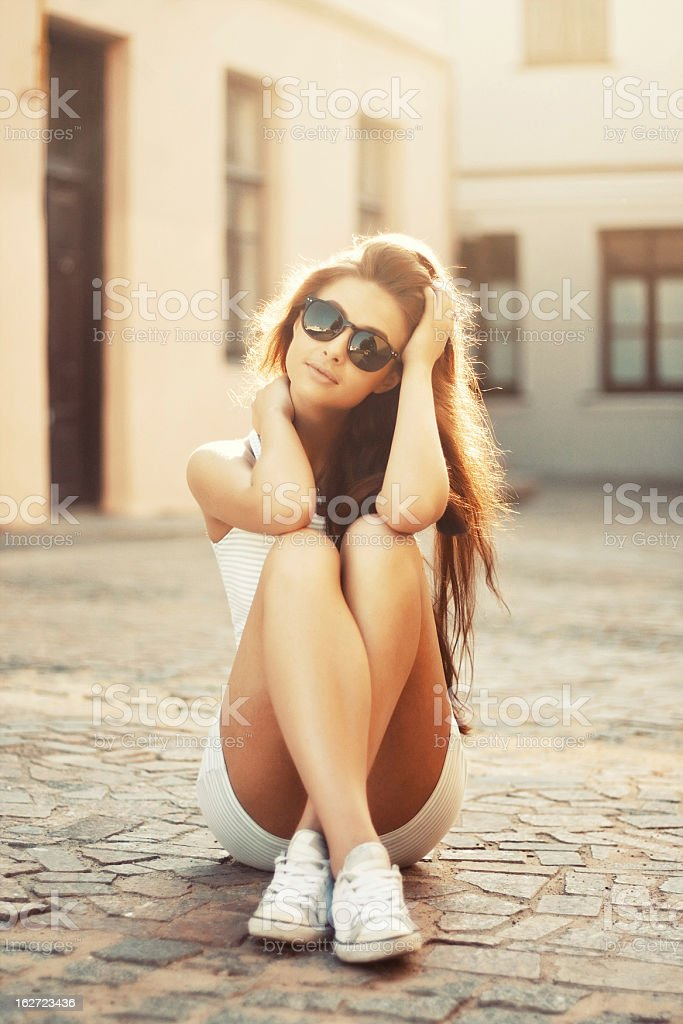 Beautiful girl sitting on the ground stock photo