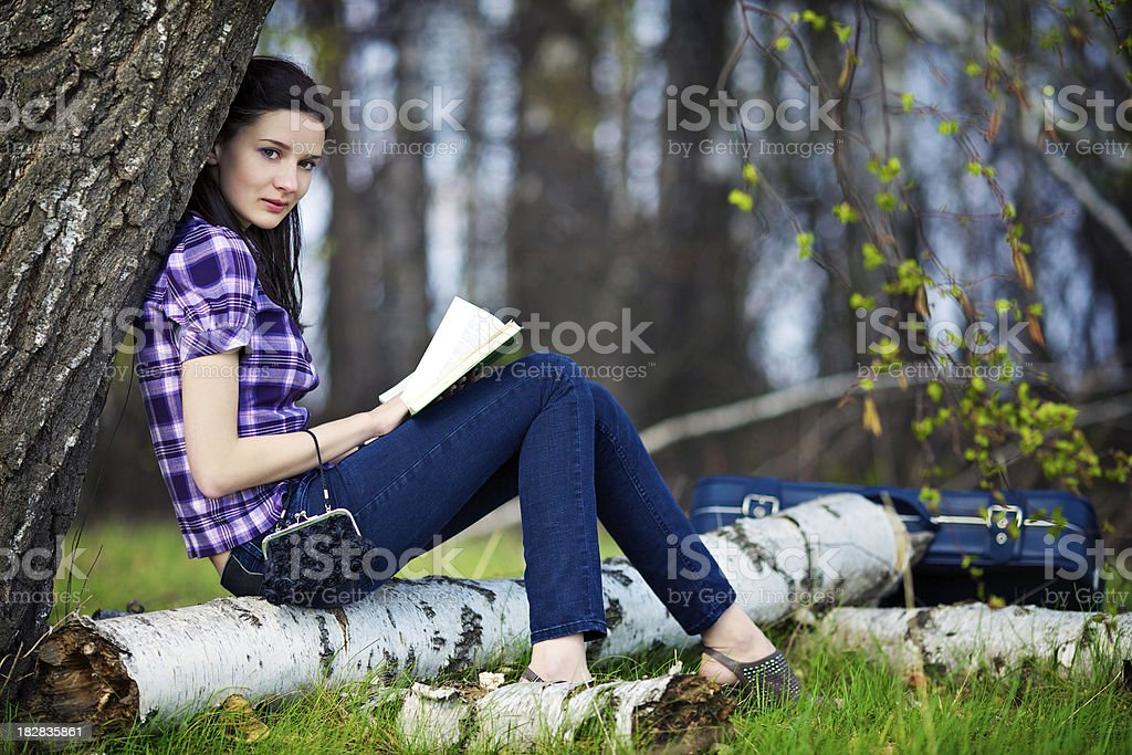 Beautiful girl sitting on the lawn and read a book royalty-free stock photo