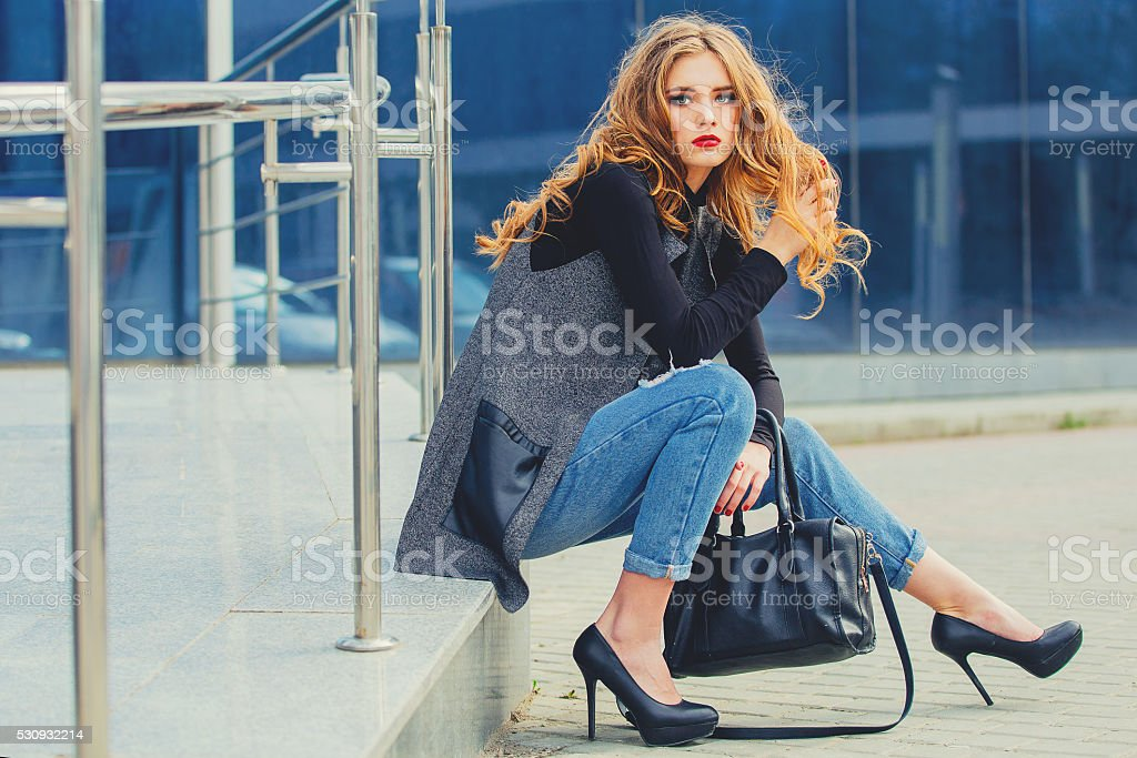 Beautiful girl sitting on the stairs near the business center. stock photo