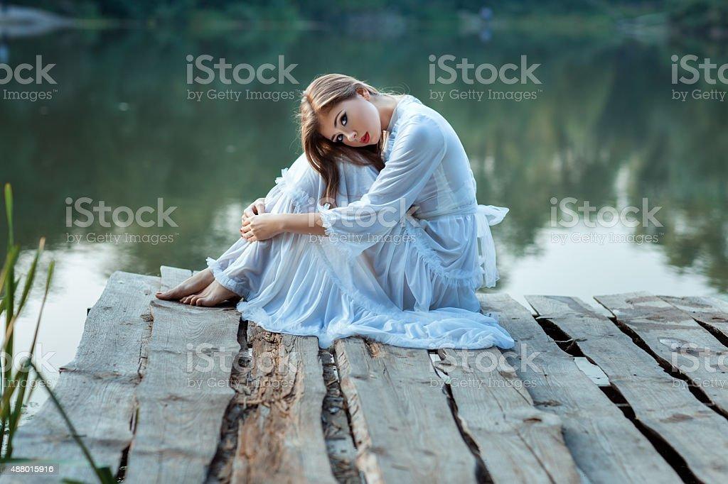 Beautiful girl sitting on the wharf bored. stock photo
