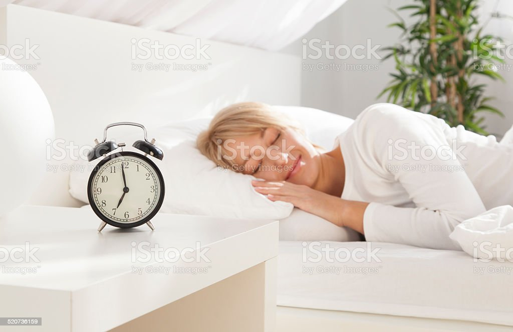 beautiful girl sleeping in her bed.  focus on clock stock photo
