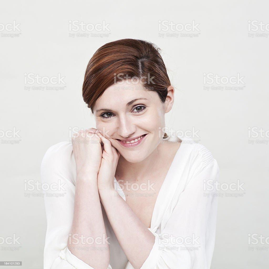 Beautiful girl smiling at camera sitting down _ Vertical royalty-free stock photo