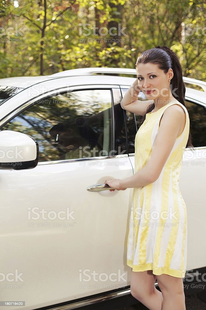 Beautiful girl standing by her car. royalty-free stock photo