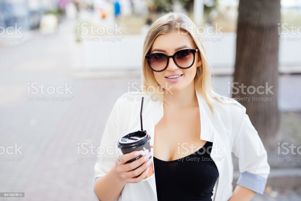 Beautiful girl standing on the street with coffee and glasses. stock photo