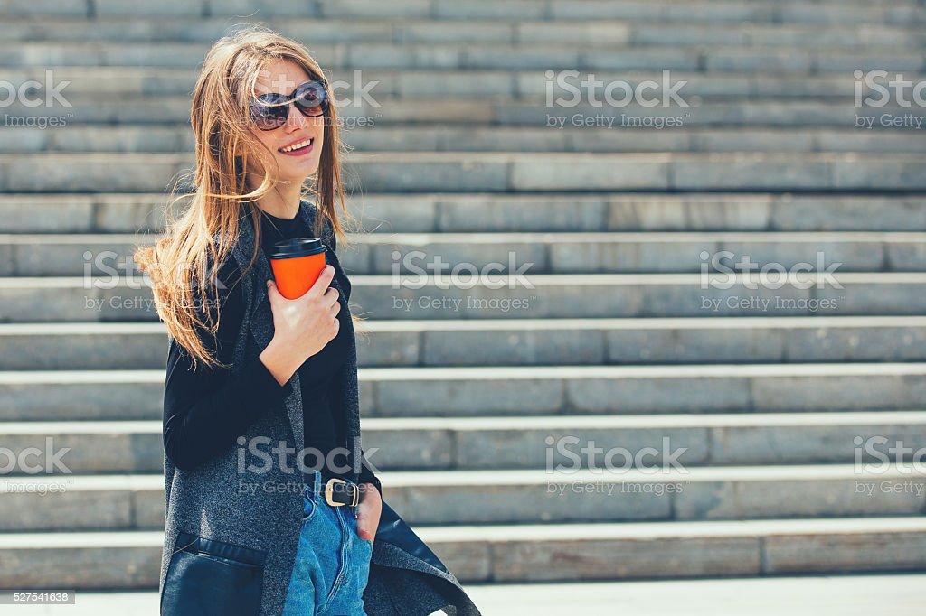 Beautiful girl standing on the street with coffee. stock photo