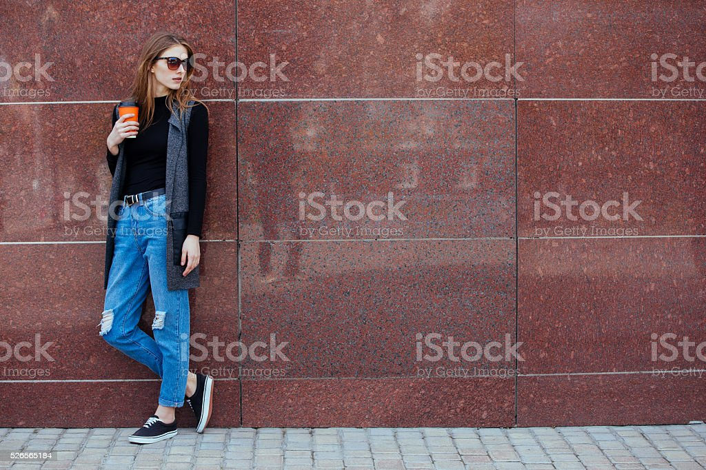 Beautiful girl stands against the wall with coffee. stock photo