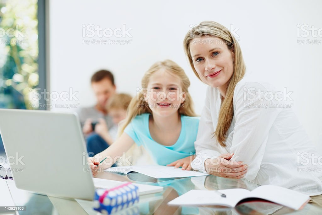 Beautiful girl studying with mother at home royalty-free stock photo