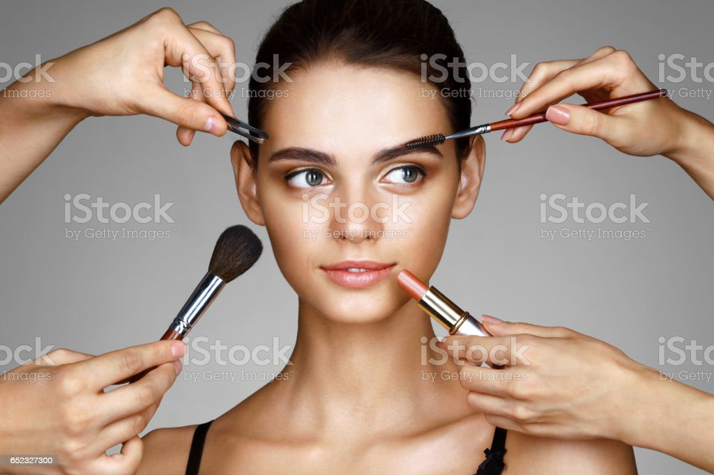 Beautiful girl surrounded by hands of makeup artists with brushes and lipstick near her face. stock photo