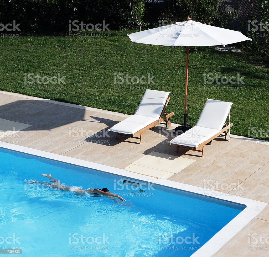 Beautiful girl swimming in a resort pool royalty-free stock photo
