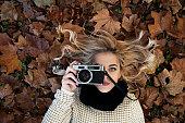 Beautiful girl taking photos with retro camera