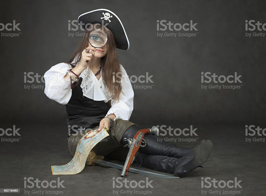 Beautiful girl the pirate looks through a magnifier stock photo