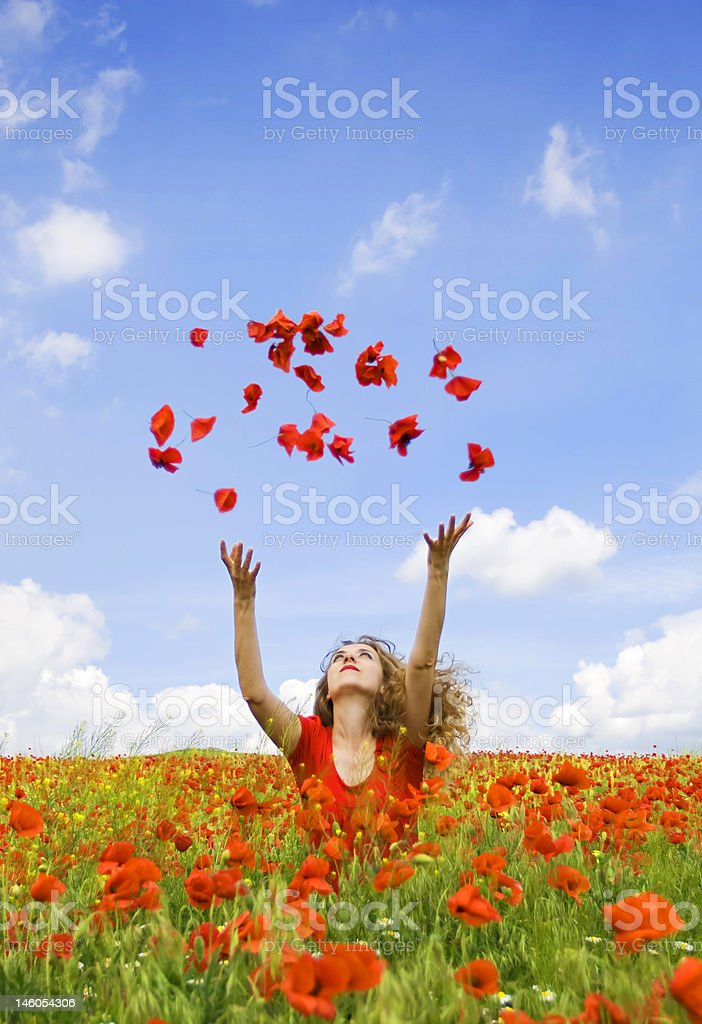 beautiful girl throwing poppies in the air royalty-free stock photo