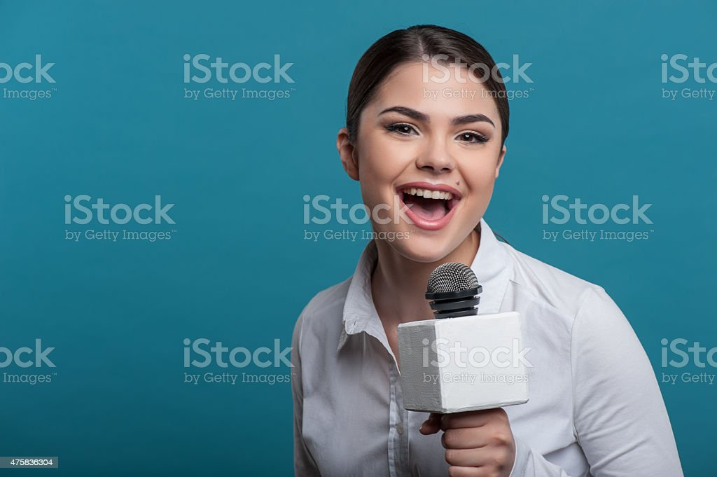 Beautiful girl TV journalist with pretty smile is reporting stock photo