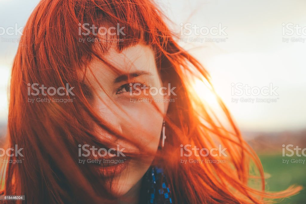 Beautiful girl upland with red hair blown by wind stock photo