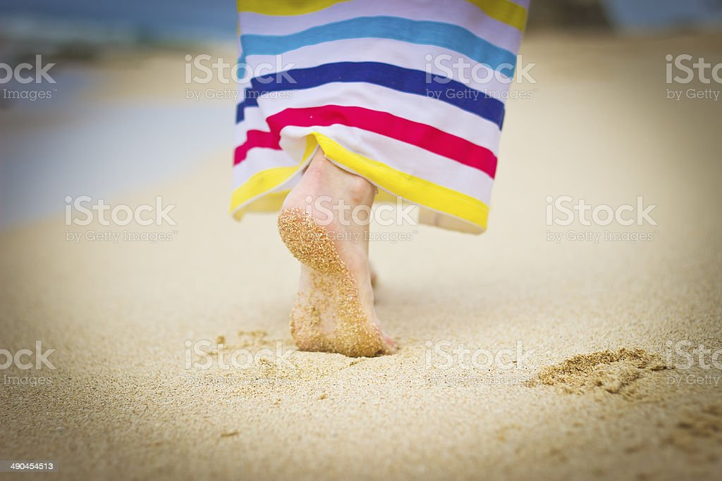 Beautiful girl walking in colorful dress on the beach stock photo