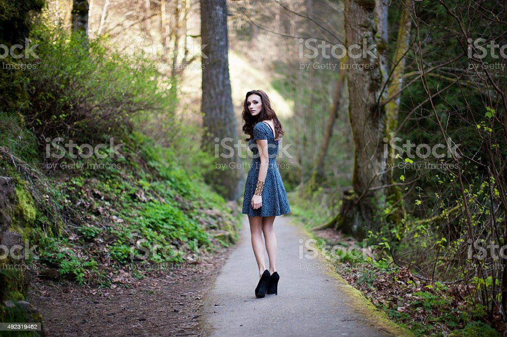 Beautiful Girl Walking on a Path in the Woods stock photo