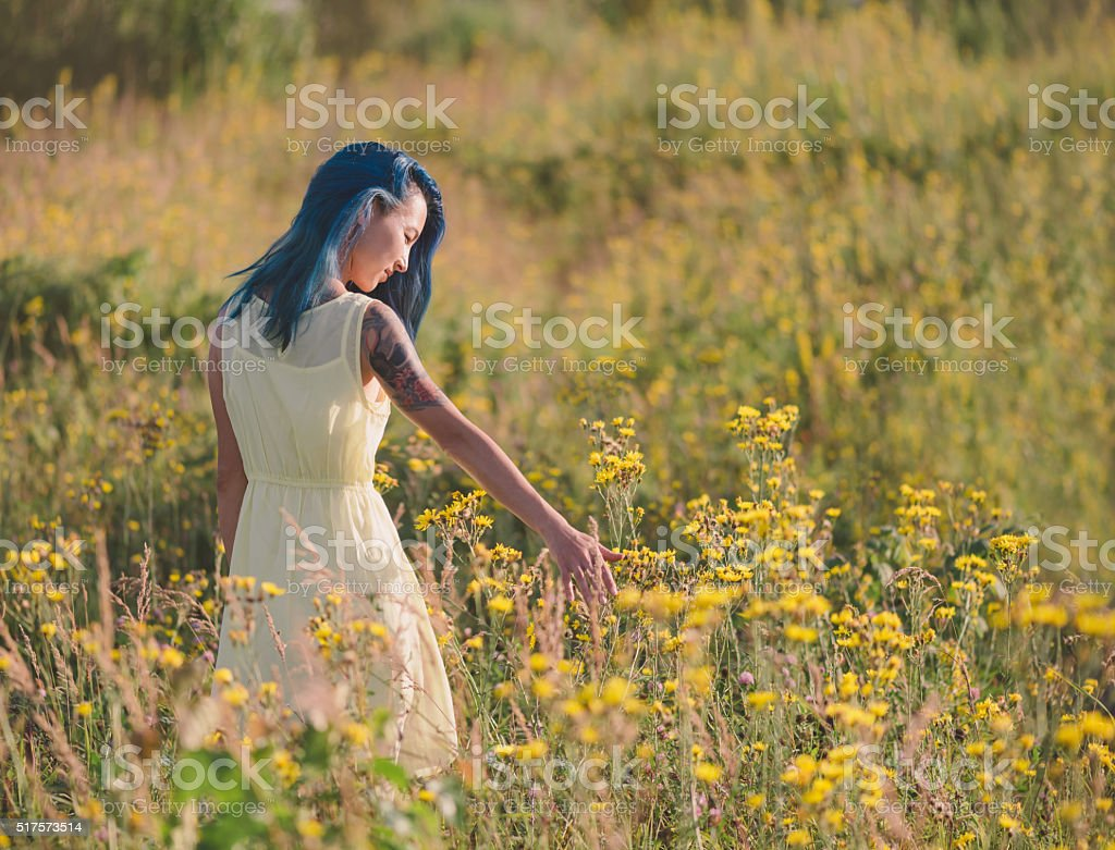 Beautiful girl walking on flower field stock photo