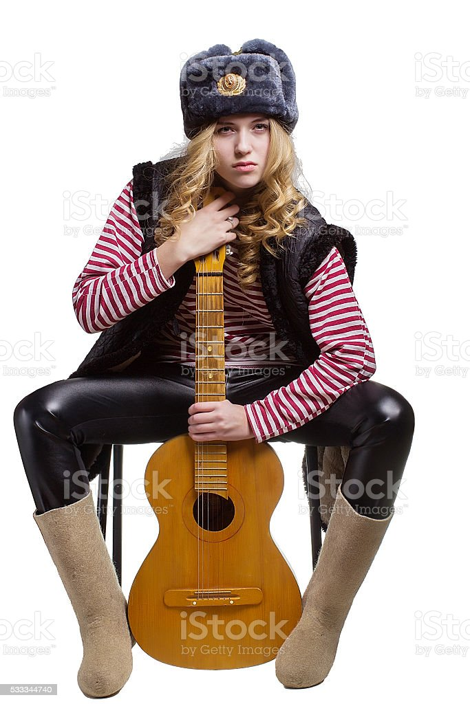 Beautiful girl wearing a soviet soldier's cap  with a guit stock photo