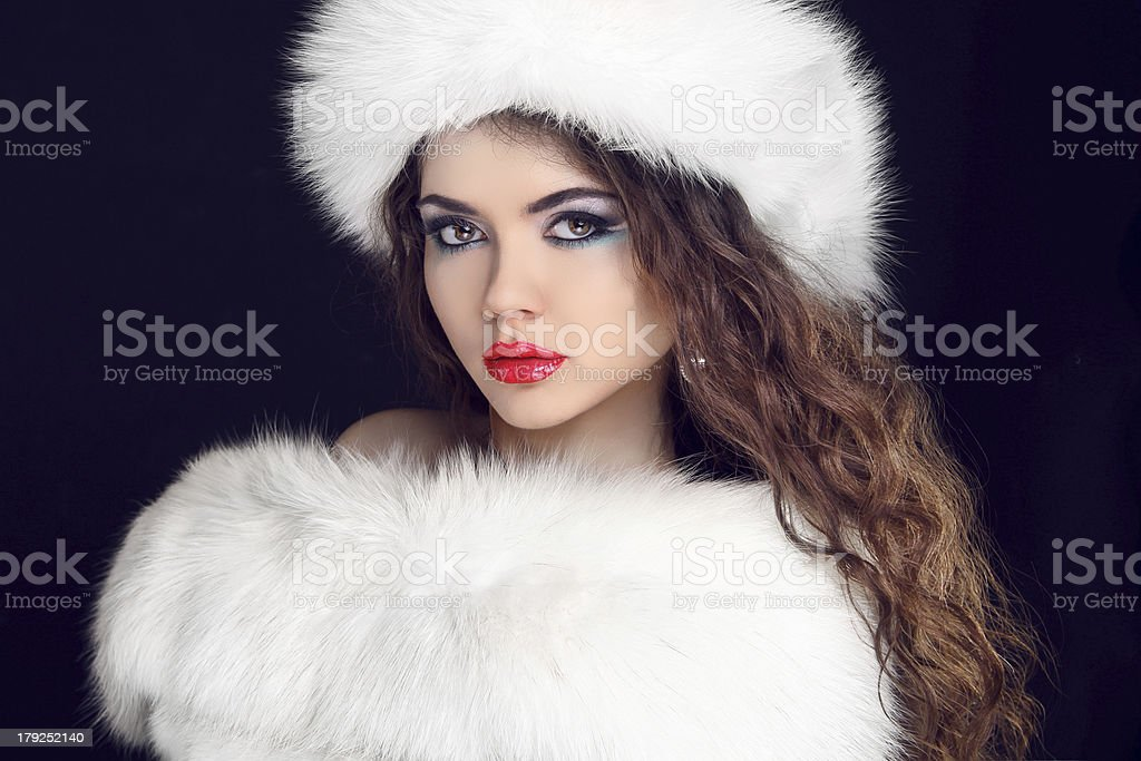 Beautiful Girl wearing in White Fur Coat and Furry Hat. royalty-free stock photo
