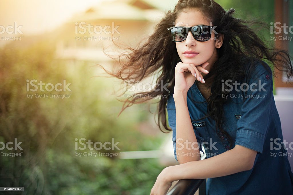 Beautiful girl wearing sunglasses enjoying fresh air in balcony. stock photo