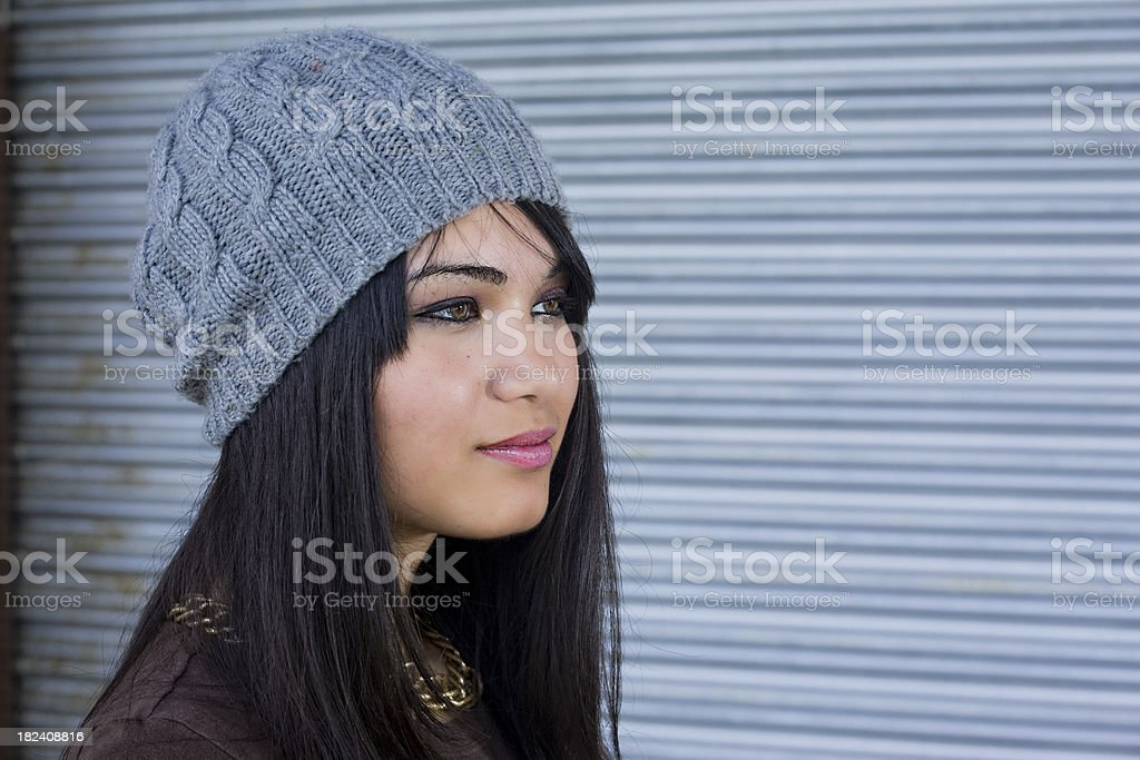 Beautiful Girl with a stylish grey knit hat in profile royalty-free stock photo