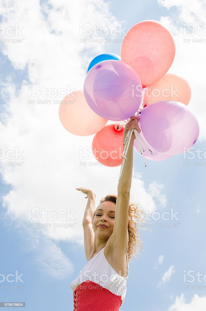 beautiful girl with balloons flying in the sky stock photo