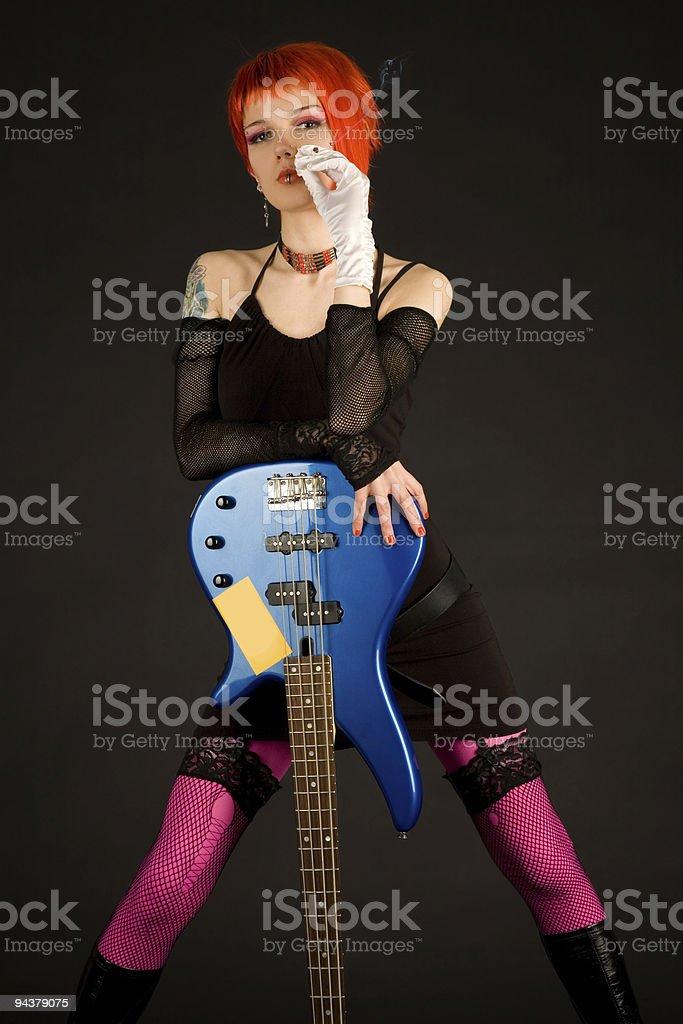 Beautiful girl with bass guitar smoking stock photo