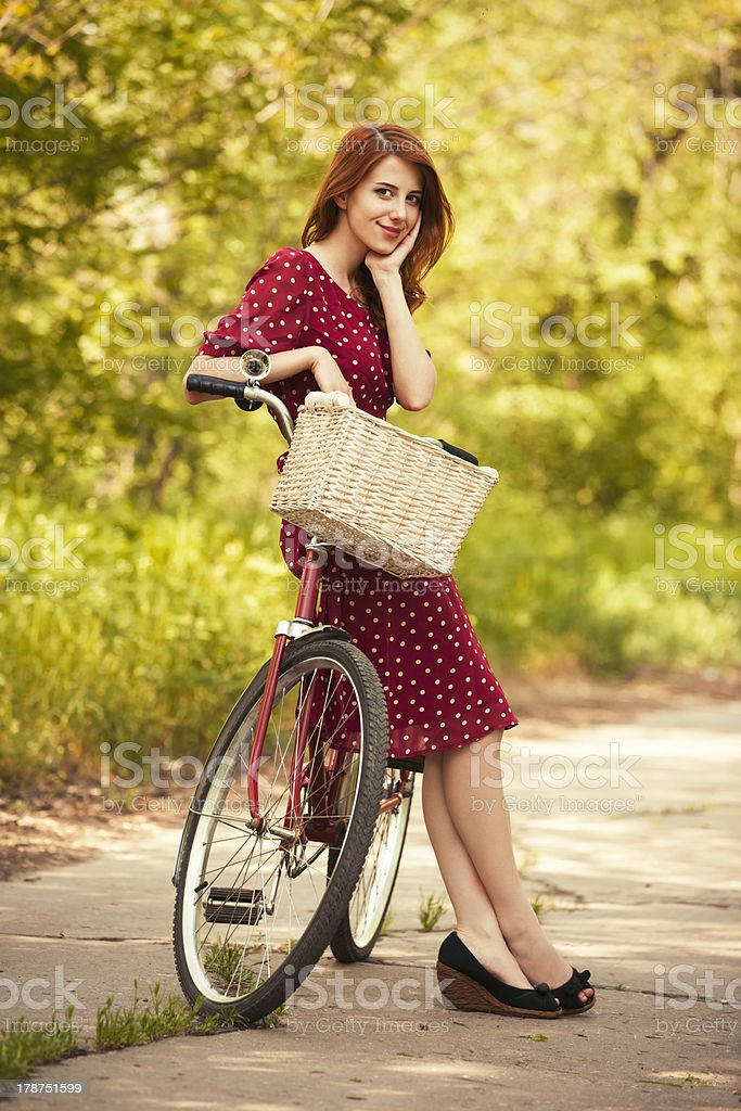 Beautiful girl with bike at countryside. stock photo