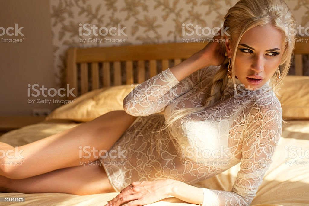 beautiful girl with blond hair in  lingerie lying on bed stock photo