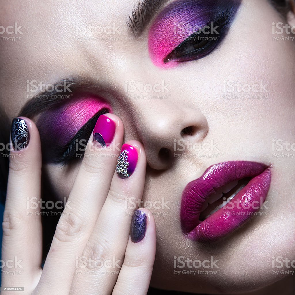 Beautiful girl with bright creative fashion makeup and colorful nail stock photo