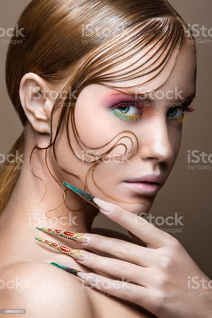 Beautiful girl with bright fashion make-up, creative hairstyle, long stock photo