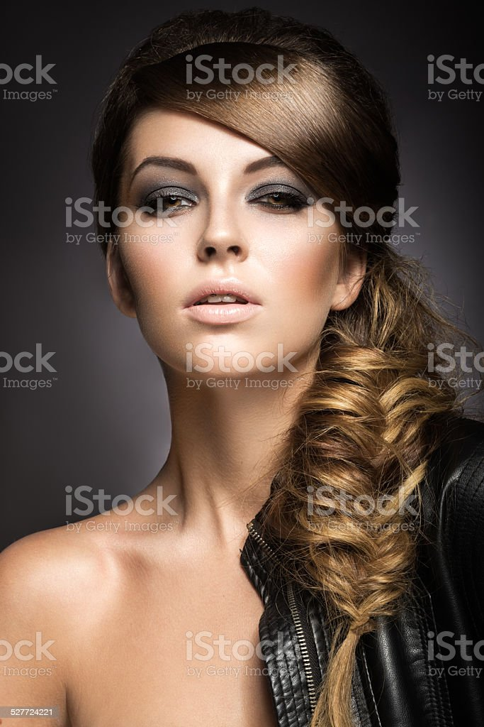 Beautiful girl with bright make-up, perfect skin and braid hairstyle stock photo