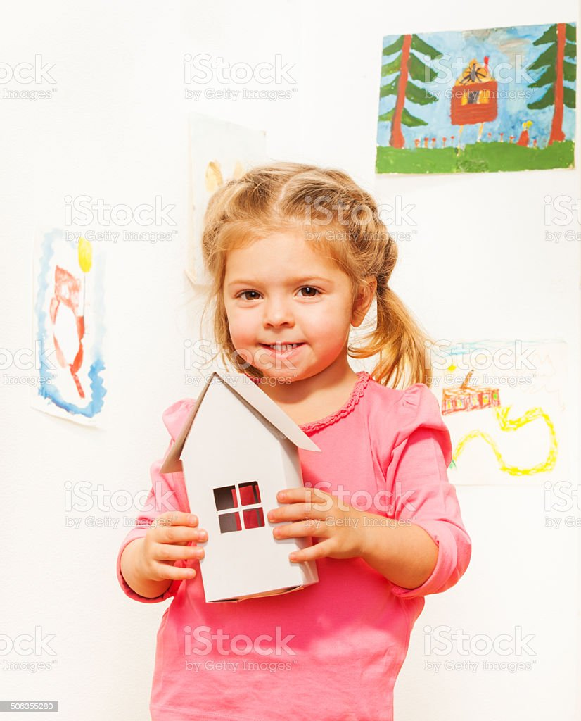 Beautiful girl with cardboard white doll house stock photo