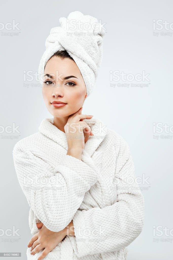 Beautiful girl with dark hair wearing bath robe and towel stock photo
