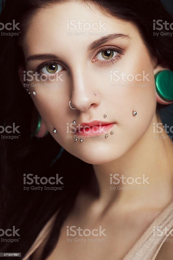 Beautiful girl with face piercing and plugs royalty-free stock photo