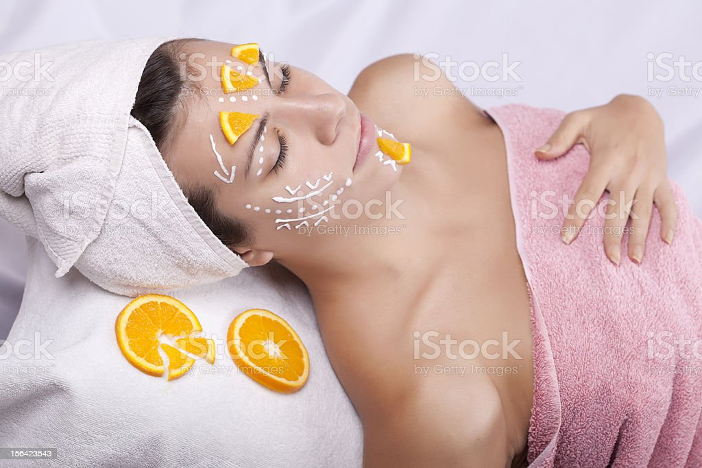 Beautiful girl with facial mask and slices of orange royalty-free stock photo