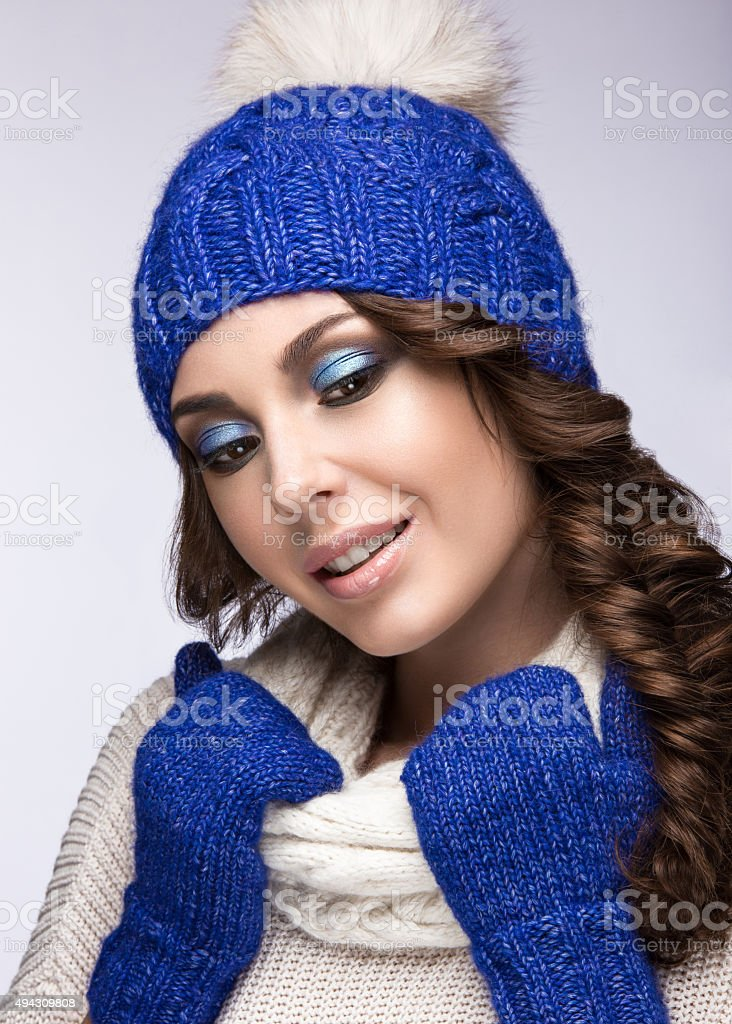 Beautiful girl with gentle make-up in winter blue knit cap. stock photo