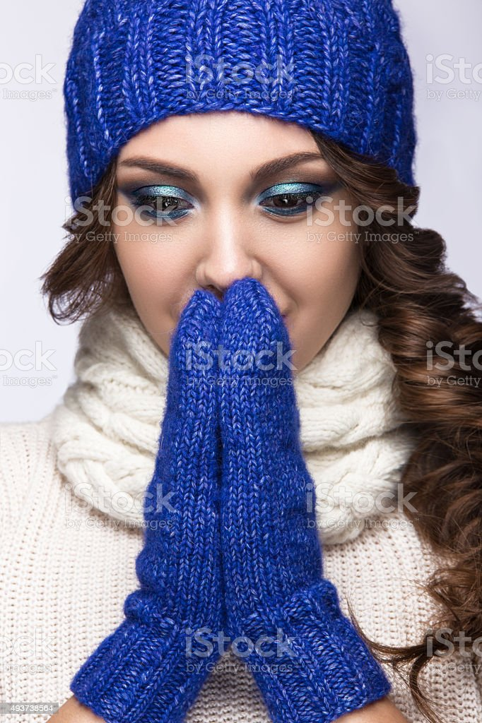 Beautiful girl with gentle makeup, smile in blue knit hat. stock photo