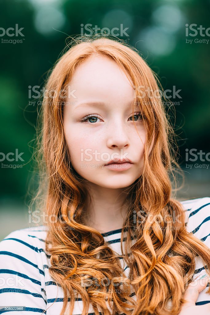 Beautiful girl with green eyes and long curly red hair stock photo
