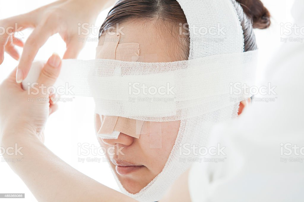 Beautiful girl with head bandages patient cosmetology stock photo