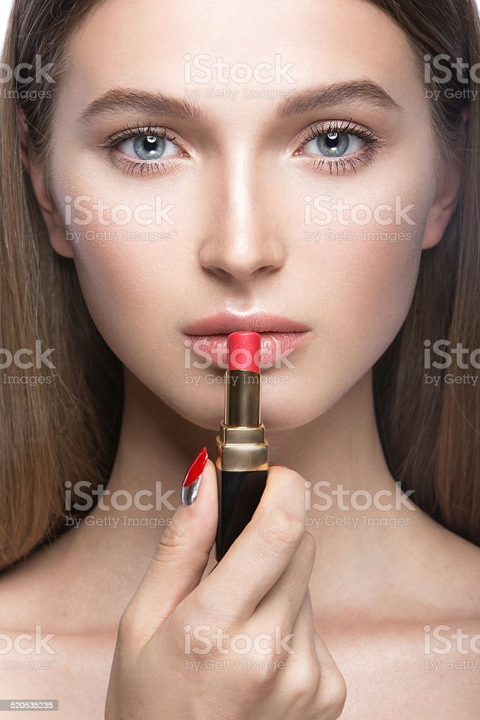 Beautiful girl with light makeup and lipstick in hand stock photo